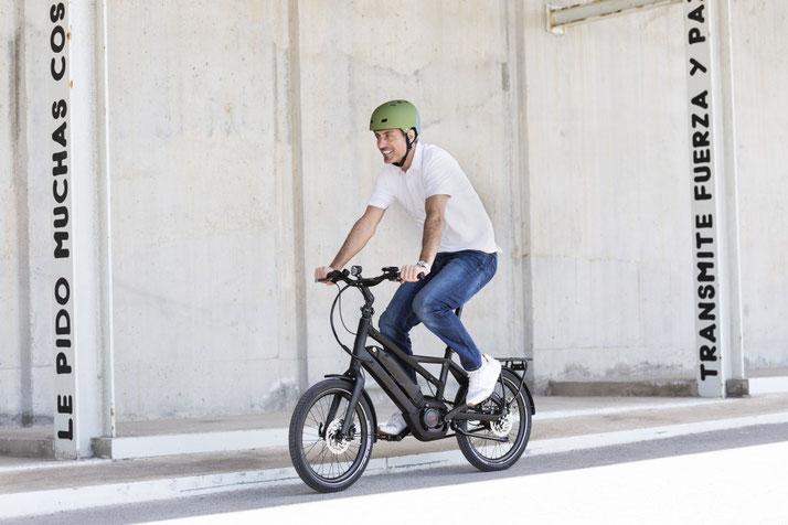 Mann fährt auf seinem Winora Radius Tour durch die Stadt