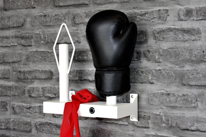 Boxing gloves on a black dryer bolted to a grey brick wall