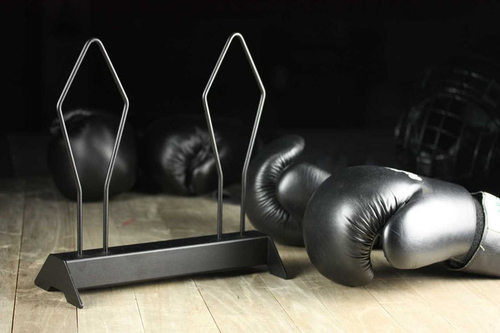 black boxing glove rack on a wooden surface and boxing gloves in the background