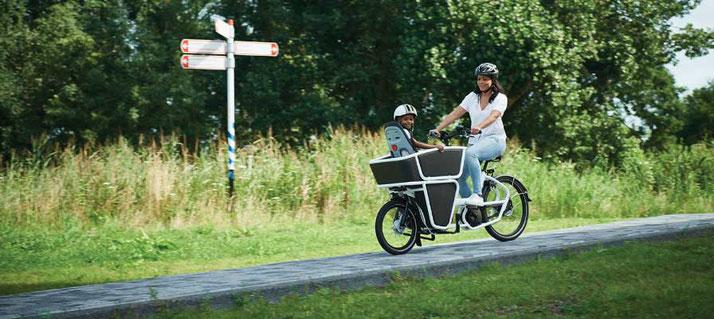 Frau fährt mit ihrem Urban Arrow Shorty und einem kleinen Jungen auf einem Weg entlang
