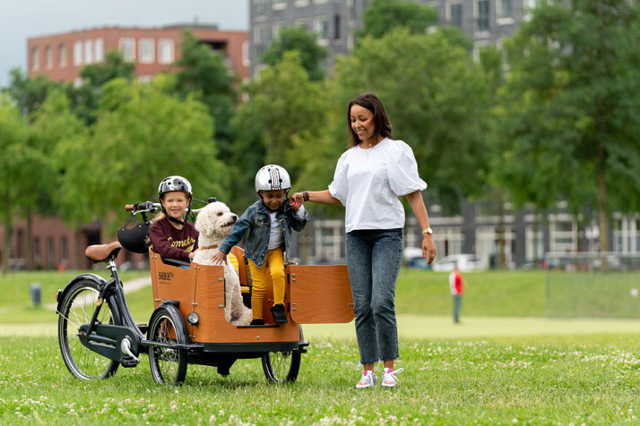 Lastenrad von Babboe mit Mutter, zwei Kindern und Hund im Park unterwegs