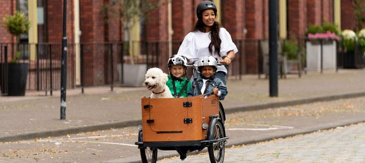 Babboe Lastenrad - Frau mit ihren beiden Kindern und Hund unterwegs