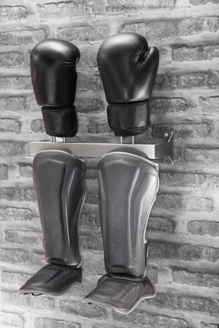 stainless boxing glove display rack bolted to a grey brick wall