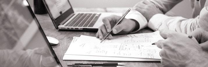 Detailaufnahme zweier Personen mit Stiften in der Hand über Arbeitspapieren