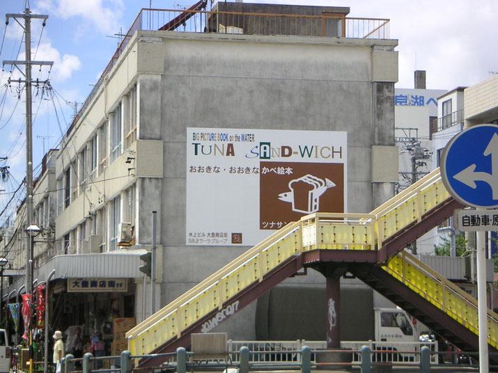 豊橋にある水上ビル壁面のストーリー性のある物語パネル看板