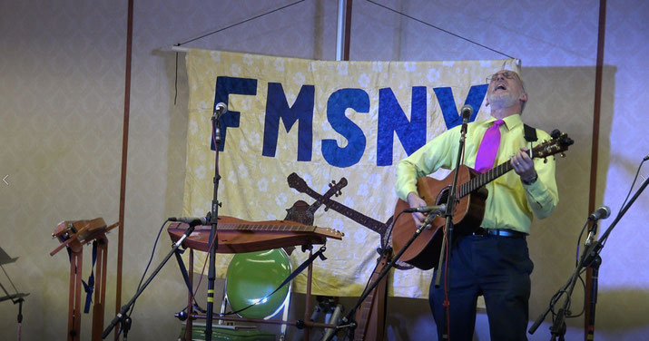 Sam, in a painfully yellow shirt and magenta tie, playing guitar on a song that compels great enthusiasm, on stage at a folk festival in New York.
