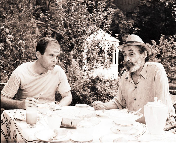 Zwei Männer am Tisch vor einem Gartenpavillon
