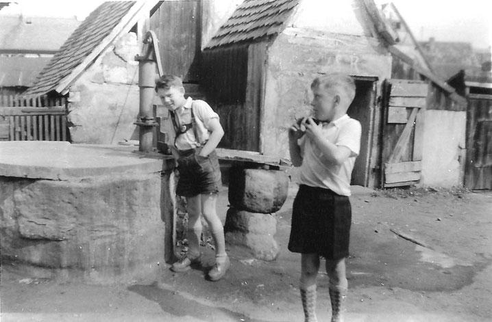 Im Hof des Häuschens Fürther Straße 17: am Brunnen ich im mittleren Schlüsselkind-Alter; im Vordergrund mein Nachbar-Spielkamerad Stefan Müller