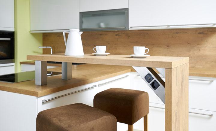 """Beispielanwendung in der Küche mit einem Tresen. Links die gerade Konsole """"BSG"""" rechts die Rückwandkonsole """"RWSC"""" mit 2fach USB-Charger und einer Steckdose."""