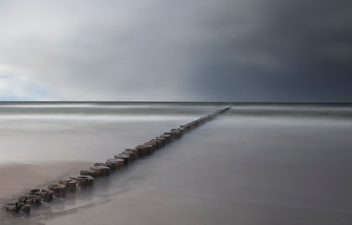 Buhnen at Zingst beach with blurred water and grey blue colors, long exposure, Baltic Sea, North East Germany, Europe