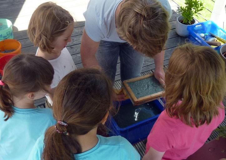Erster Schöpfversuch mit der von den Kindern hergestellten Papiermasse.