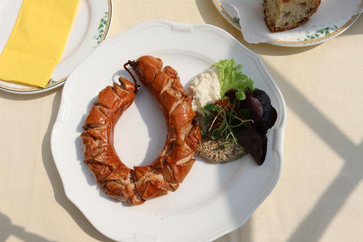 Гигансткую сосиску из местной био-свинины с горчицей и хреном подают за 8,50€