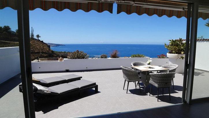 Ein toller Blick vom Wohnbereich über die sonnige Terrasse mit Gartenmöbeln auf den Atlantik.