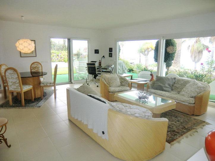 Helles Wohnzimmer mit grosser Glasfront und Blick in den Garten der Ferienvilla.