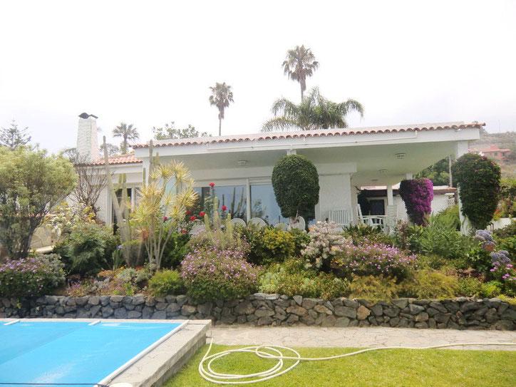 Ansicht der Ferien Villa zum Überwintern vom Pool aus über die reich bepflanzte Rabatte vor der Villa.