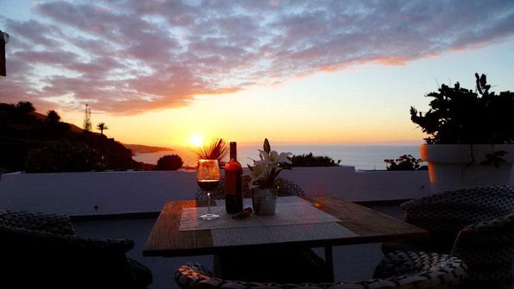 Atemberaubender und intensiver Sonnenuntergang über dem Meer von der Terrasse aus gesehen.
