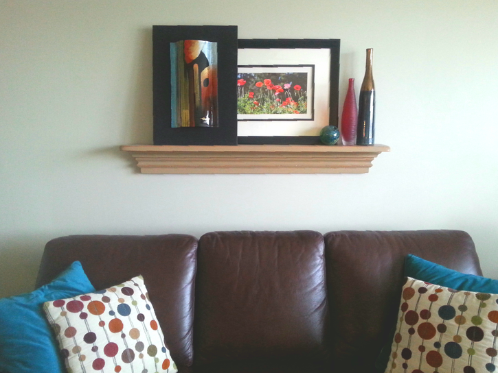 A painted picture shelf styled like a mantle gives the right proportions over the sofa and allows for changing the art and accessories.