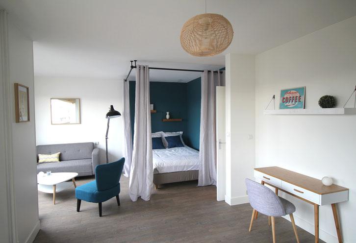 studio scandinave, coin nuit avec tringles et rideaux pour créer un baldaquin