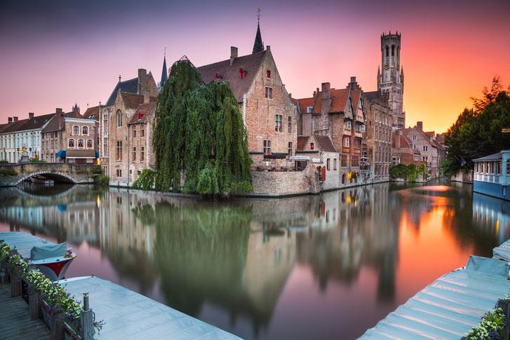Kanal mit Brücken und Booten am Rand des Stadtkerns von Brügge im Sonnenuntergang; Wirtschaftsdetektei Brügge