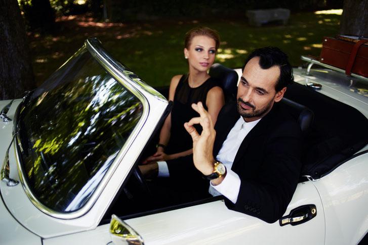 Mann in teurem Anzug mit junger Model-Frau im kleinen Schwarzen sitzt prahlerisch in einem Oldtimer-Cabriolet; Kurtz Detektei Bonn