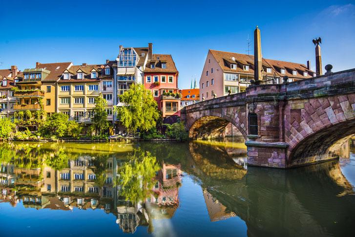 Untere Karlsbrücke, rötlich schimmernd, sehr ruhiges, spiegelndes Wasser der Pegnitz, wolkenloses Himmel; Kurtz Detektei Nürnberg