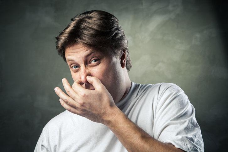 Mann in weißem T-Shirt hält sich die Nase zu; Detektive der Kurtz Detektei Hamburg
