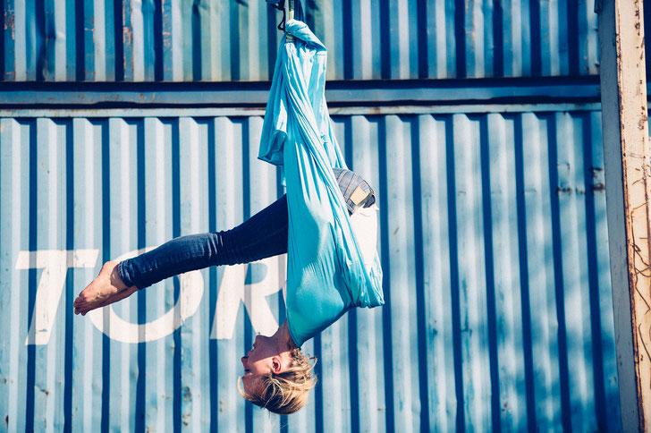 Eine Frau macht den Pilates Roll Over im Tuch in der Sonne vor einem blauen Container.