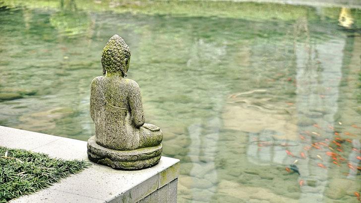 Steinerner meditierender Buddha vor einem Gewässer