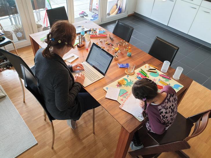 Homeoffice und Betreuung: Lehrerin mit Tochter am Küchentisch