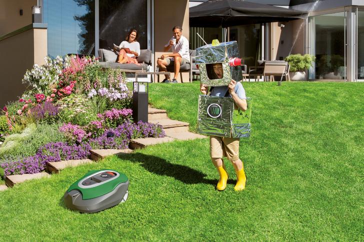 Fröhliches Kind im Garten als Roboter verkleidet mit einem Rasenroboter