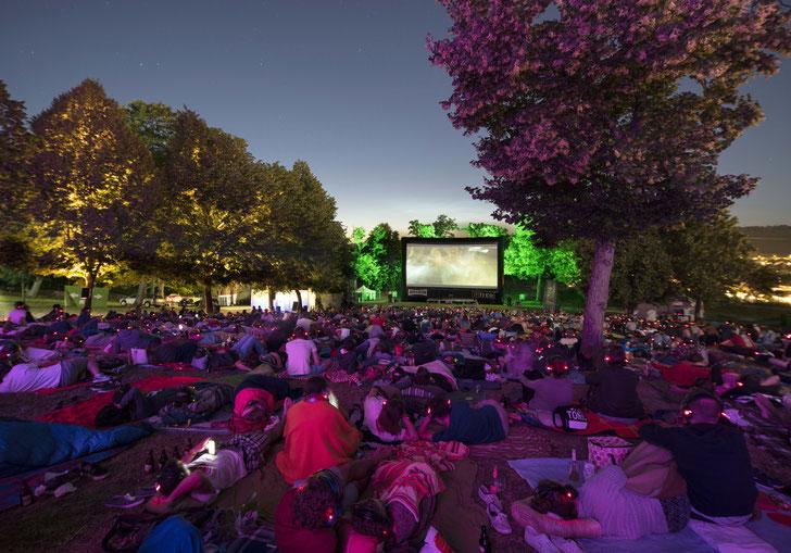"""Viele Menschen sitzen in der Dämmerung vor der großen Leinwand beim stimmungsvollen Open-Air-Kino """"Festungsflimmern"""" am Fuße der Würzburger Festung"""