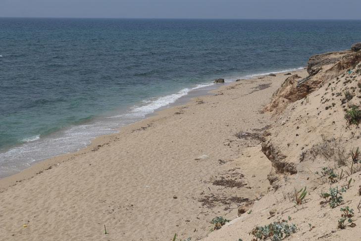 schmaler Abschnitt eines Naturstrandes von einer mit Sand bedeckte Felsküste aufgenommen. Das Meer ist leicht bewegt