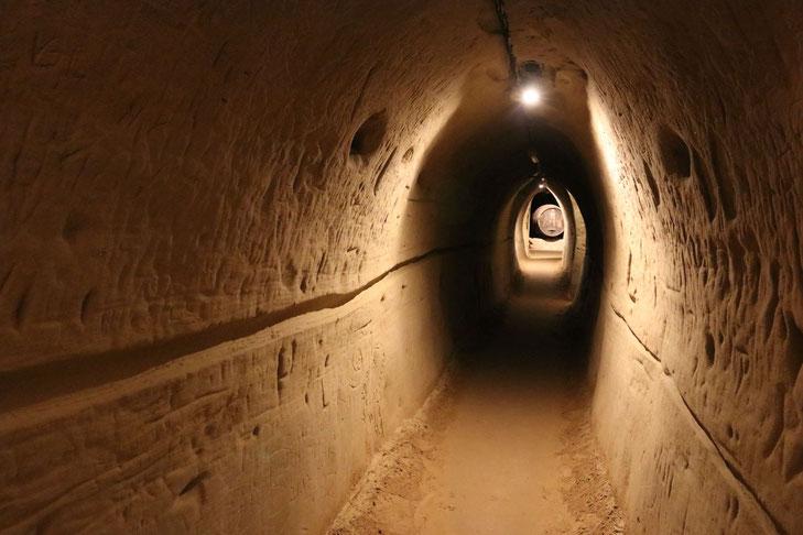 Retzer Erlebniskeller, schwach beleuchteter Tunnel mit Sandwänden und -böden