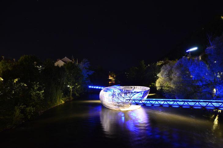 Die Murinsel in Graz bei Nacht blau beleuchtet