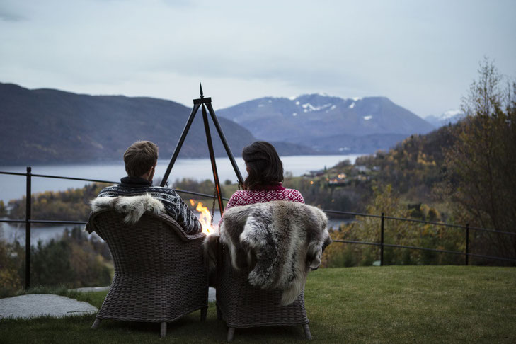 Zwei Personen von hinten vor einem Lagerfeuer in mit Fell belegten Korbstühlen mit Ausblick auf den Fjord
