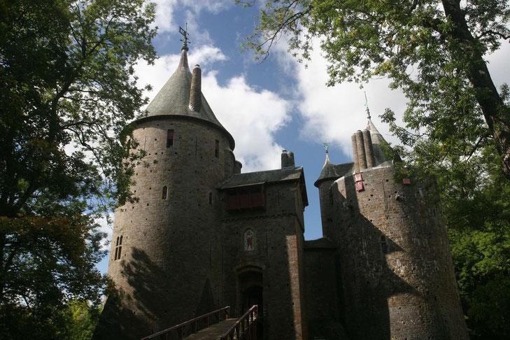 Castell Coch von außen, man sieht runde Türme mit spitzen Dächern und eine hölzerne Brücke, umrahmt von Bäumen
