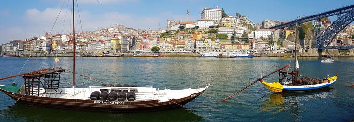 Panoramabild auf Portos Altstadt mit traditionellen Holzbooten im Vordergrund, rechts die Ponte Luis I.