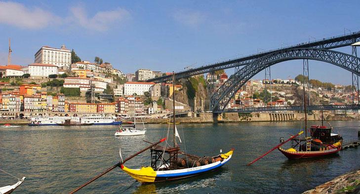 Blick auf die Altstadt von Porto mit der Bogenbrücke über den Douro im Hintergrund und alten, bunten Holzbooten im Vordergrund