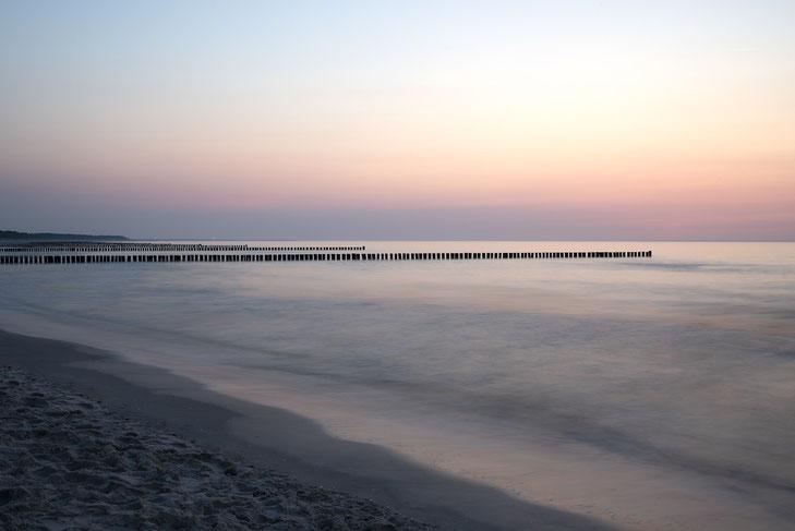 Langzeitbelichtetes Foto eines Sonnenunterganges in rosafarbenem Licht am Strand von Zingst