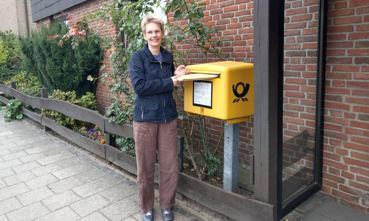 Delmenhorster Schriftstellerin Katy Buchholz steht am Briefkasten und schickt ein Buch im die Welt