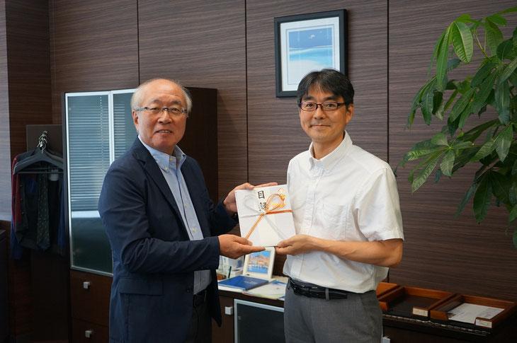 UKCホールディングス栗田伸樹社長様から里山エネルギースクール支援に活用する寄付の目録をいただきました。