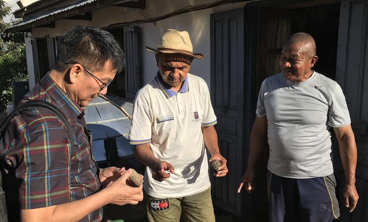 モミガラを炭化して固形化したエコ燃料の確認をするサッチョン教授、マダガスカルミライディレクター・ヘルダマンさん、バジルさん
