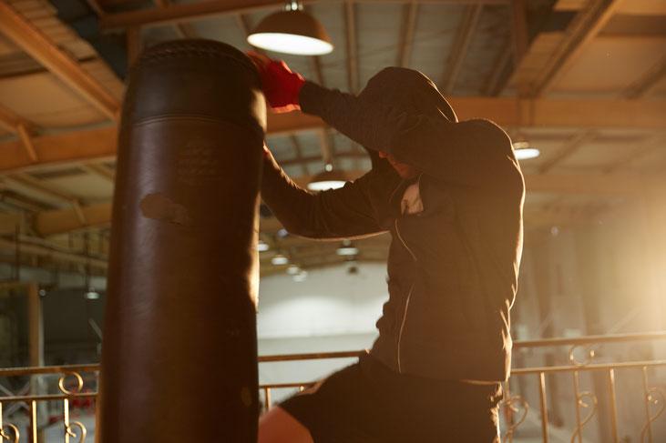 Ein Mann trainiert Muay Thai am Boxsack in einer Sporthalle. Er macht Kniestöße gegen den Boxsack.