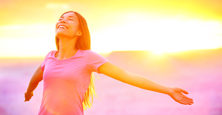 Frau lächelt bei einem Sonnenuntergang