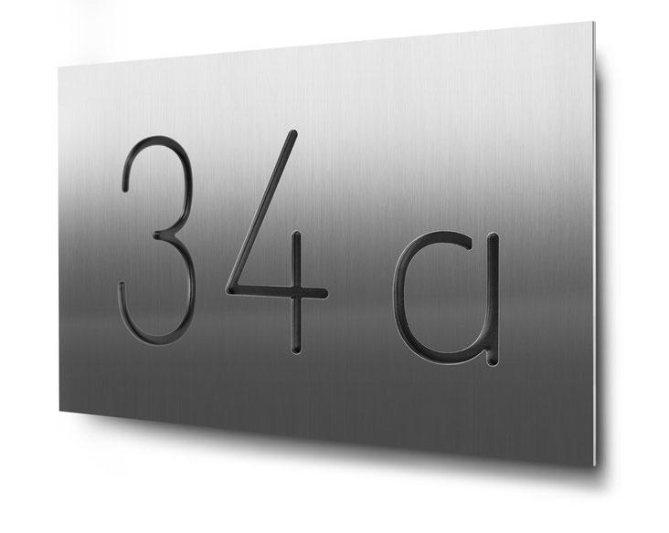 Beispiel für eine konturgeschnittene und schwarz hinterlegte dreistellige Hausnummer in Edelstahl
