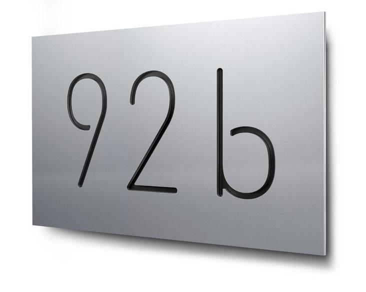 Beispiel für eine konturgeschnittene und schwarz hinterlegte dreistellige Hausnummer in Aluminium