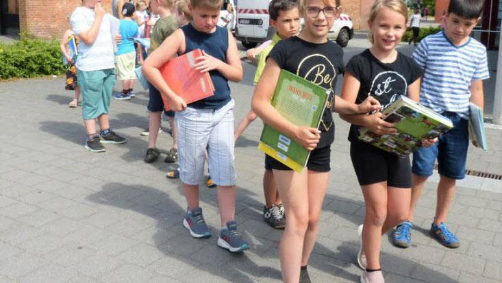 Bild Bury/Bücher bewegen: Die beiden 2. Klassen trugen die letzten Exemplare zum neuen Standort der Gemeindebücherei im Hof Lübbe