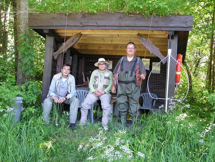 """Gapahuk - die tradtionelle norwegische Lachsfischerhütte und 3 """"Laksefisker"""" an der Surna. Beachtenswert die Keschergröße rechts außen im Bild!"""