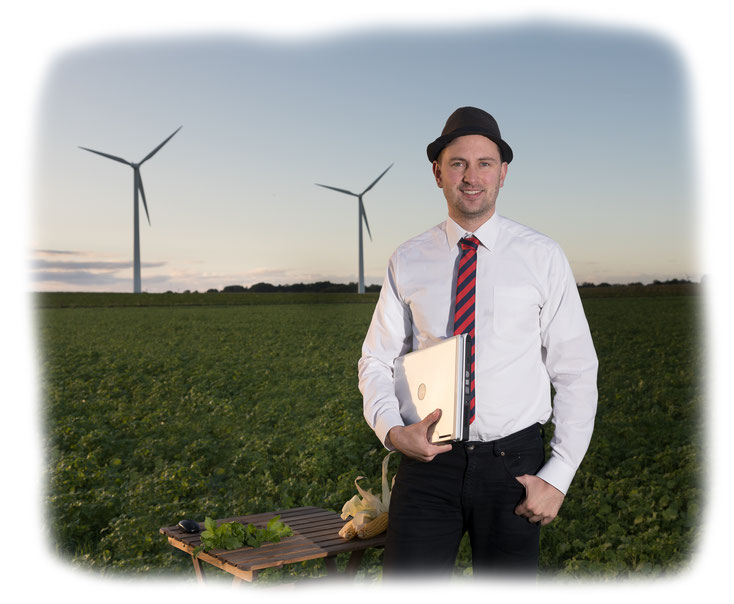 Darstellung des Geschäftsführers (Christoph Backhaus) auf einem Kartoffelfeld und im Hintergrund 2 große Windanlagen.