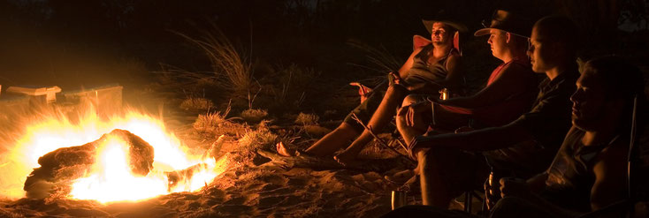 Photo: Four young men sitting around a campfire.